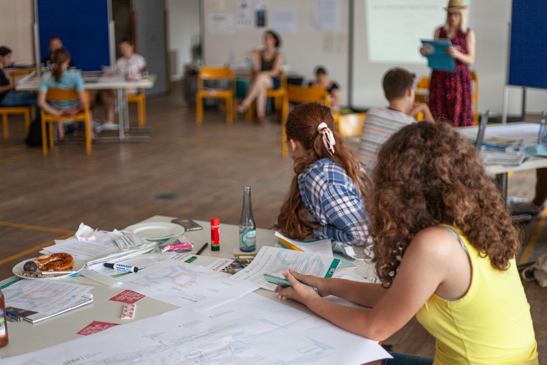 Hier sind junge Teilnehmende an einem Workshop zu sehen. Die Tische stehen in unserer Turnhalle weit auseinander, so dass man die Abstandsregeln einhalten kann
