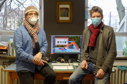 Zwei Männer mit Schal und Atemschutzmaske sitzen auf einem Tisch, hinter ihnen ein Bildschirm.