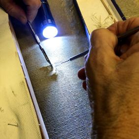 Zwei Hände bearbeiten mit zwei feinen Werkzeugen ein Stück Leinwand