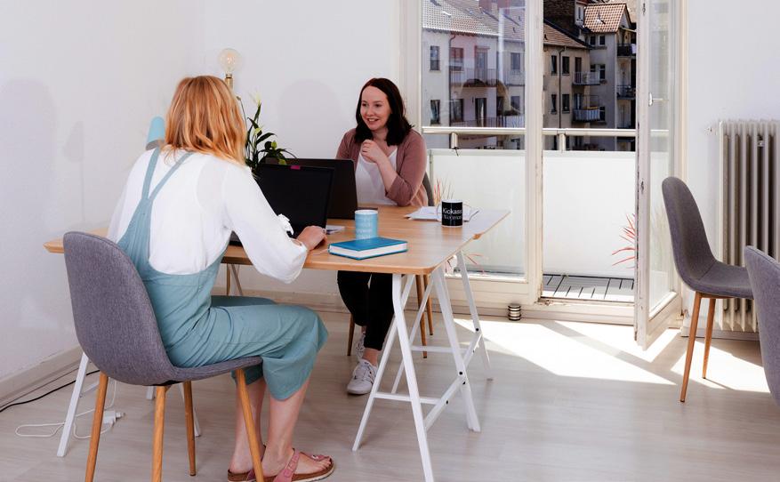 Zwei Frauen sitzen einander an einem Tisch gegenüber.