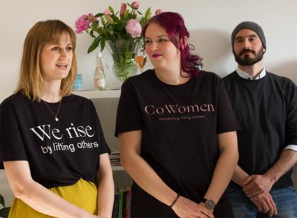 Drei Besucher in dunklen T-Shirts stehen vor einem Regal mit einer Blumenvase.