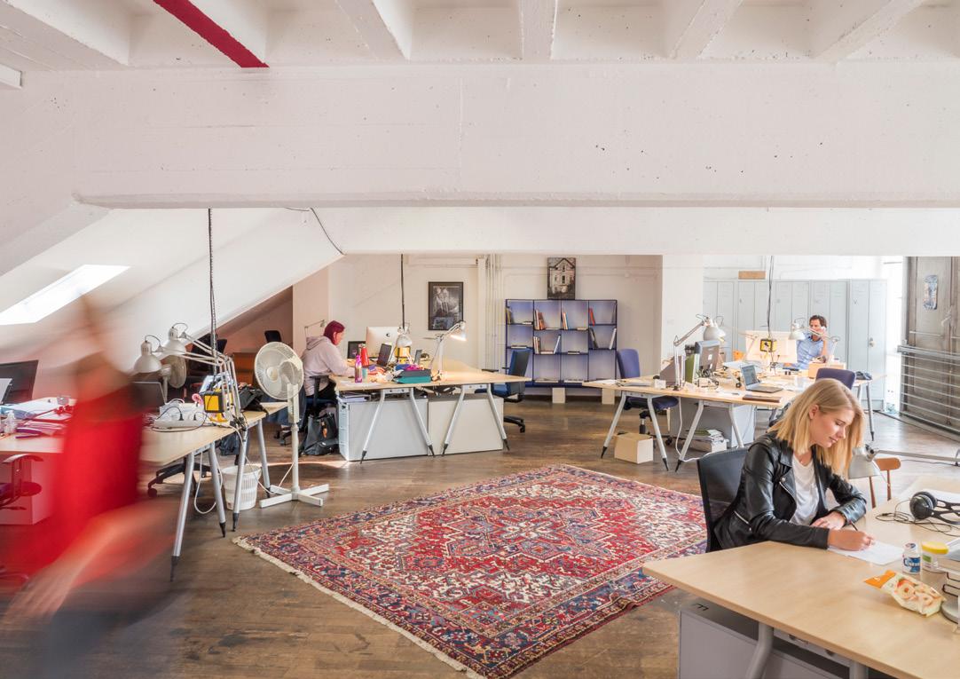 Um die Mitte eines Raumes herum stehen fünf Schreibtische, an denen Personen arbeiten.