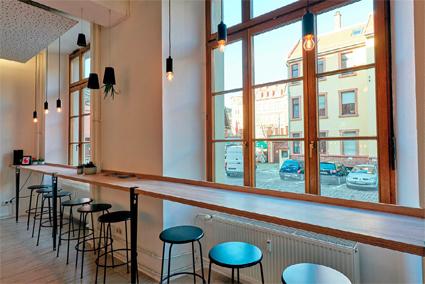 Eine Reihe Barhocker stehen vor einem langen Tisch direkt vor sehr hohen Fenstern.