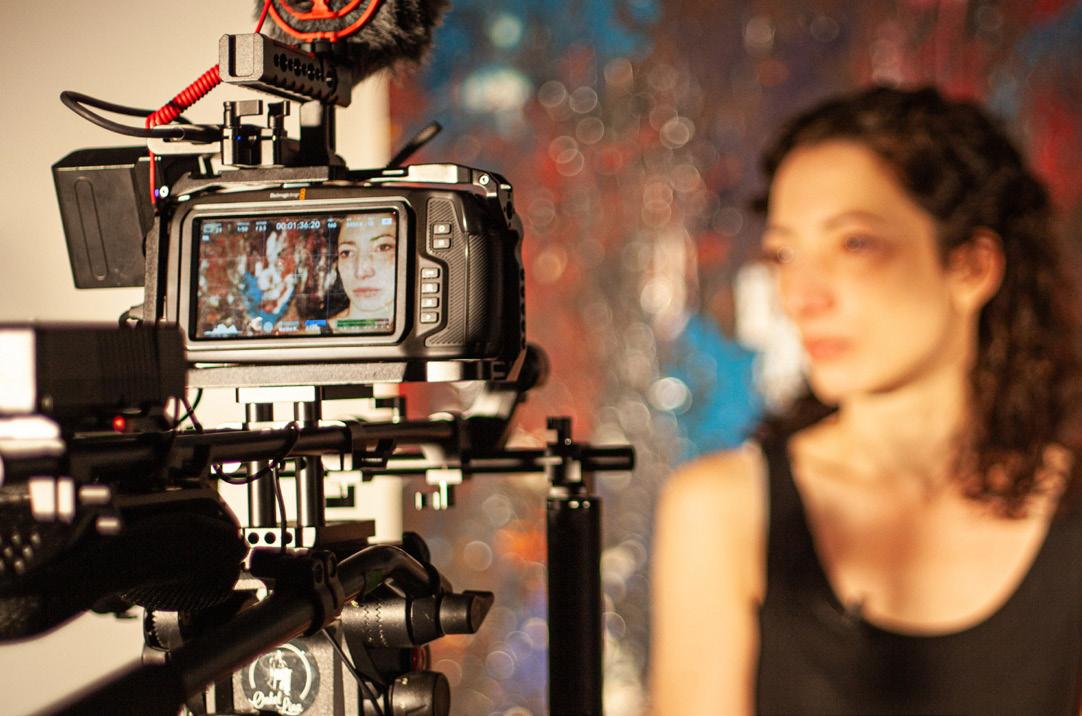 Eine Kamera nimmt das Gesicht einer Frau auf, das undeutlich im Hintergrund zu sehen ist.