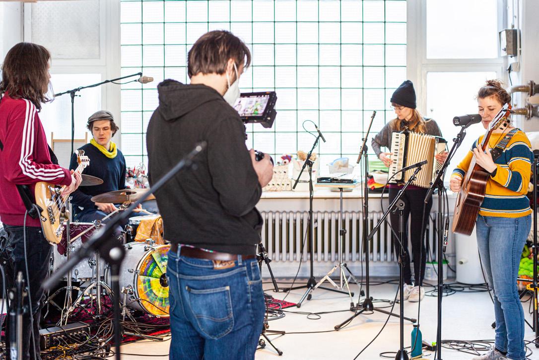 Ein Kameramann und vier Musikerinnen und Musiker stehen mit Aufnahmetechnik in einem Raum.
